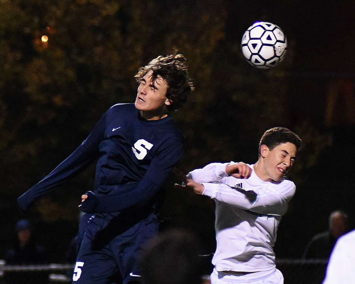 Staples' Anton Mahr, left, and Norwalk's Lucas Araujo battle for a head ball during Monday's FCIAC boys soccer game at Testa Field in Norwalk. The game ended in a 1-1 tie.