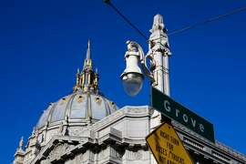 A historic street lamp is seen, with City Hall behind it, on Van Ness Avenue and Grove Street in San Francisco, California, on Monday, Oct. 10, 2016.