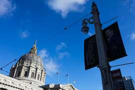 A historic street lamp is seen, with City Hall behind it, on Van Ness Avenue in San Francisco, California, on Monday, Oct. 10, 2016.