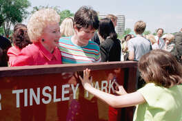 Angela Daniel traces the name of the park dedicated to her grandmother, Eleanor Tinsley, who looks on with her daughter, Marilyn Daniel, in 1998.