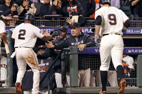 San Francisco Giants' Denard Span is welcomed back to dugout by manager Bruce Bochy after scoring on Brandon Belt's sacrifice fly in 5th inning against Chicago Cubs' Jake Arrieta during Game 3 of the National League Division Series at AT&T Park in San Francisco, Calif., on Monday, October 10, 2016.