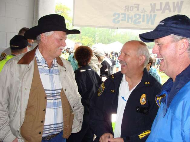 Standing in the pavilion at Jennings Beach on Saturday, Frank E. Shankwitz, left (in cowboy hat), of Arizona, founder of the Make-a-Wish Foundation, talks with Fairfield Police Chief Dave Peck, center, and Mike Burke, right, chief executive officer of the organization's Connecticut chapter, about granting a wish to a young boy 30 years ago, which led to the creation of the national nonprofit that grants wishes to children with life-threatening conditions. The organization celebrates its 30th anniversary this year. Photo: Contributed Photo, Contributed Photo / Meg Barone / Fairfield Citizen