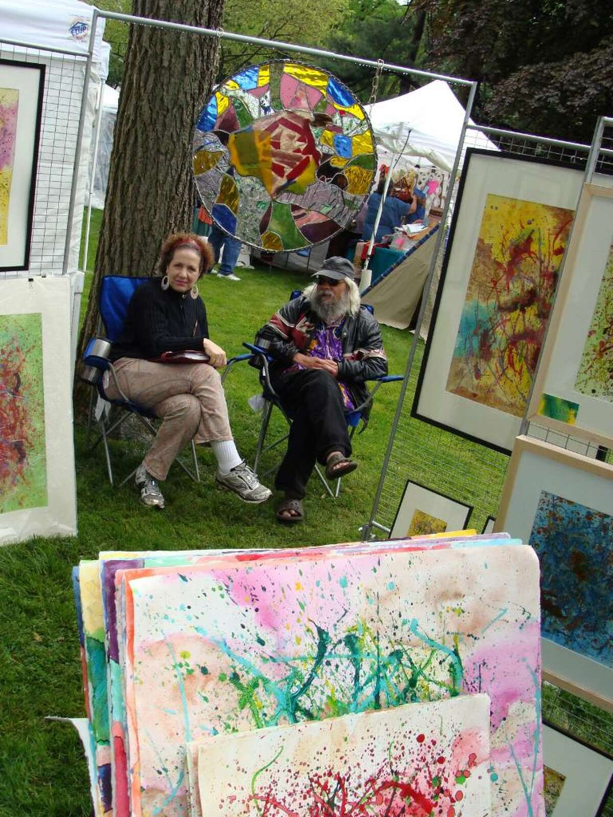 """Lisa Bershtein, left, and Eduardo A. LaChall Bencomo sit amidst Bencomo's creations on """"art on paper"""" and """"art with glass and stone"""" at the arts and crafts market on Saturday."""