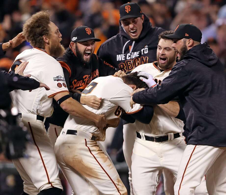 San Francisco Giants celebrate Joe Panik's game-winning double in 13th inning of 6-5 win over Chicago Cubs during Game 3 of the National League Division Series at AT&T Park in San Francisco, Calif., on Monday, October 10, 2016. Photo: Scott Strazzante, The Chronicle