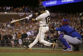 San Francisco Giants' Joe Panik (12) hits a double to score Brandon Crawford in front of Chicago Cubs catcher David Ross during the thirteenth inning of Game 3 of baseball's National League Division Series in San Francisco, Monday, Oct. 10, 2016. The Giants won 6-5 in 13 innings. (AP Photo/Ben Margot)