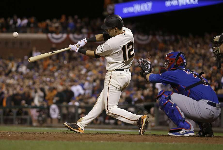 San Francisco Giants' Joe Panik (12) hits a double to score Brandon Crawford in front of Chicago Cubs catcher David Ross during the thirteenth inning of Game 3 of baseball's National League Division Series in San Francisco, Monday, Oct. 10, 2016. The Giants won 6-5 in 13 innings. Photo: Ben Margot, Associated Press
