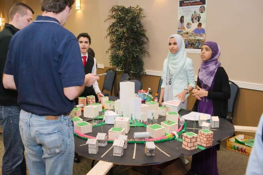 Inman Academy - Webster campus students Abraham Albaba, Nada Shalaby, and Fatima Islam present their project to judges during the Future City Competition, Tomorrow's Transit: Design A Way To Move People In And Around Your City regional finals at Johnson Space Center Gilruth Center Saturday, Jan. 18. Photo: KIRK SIDES