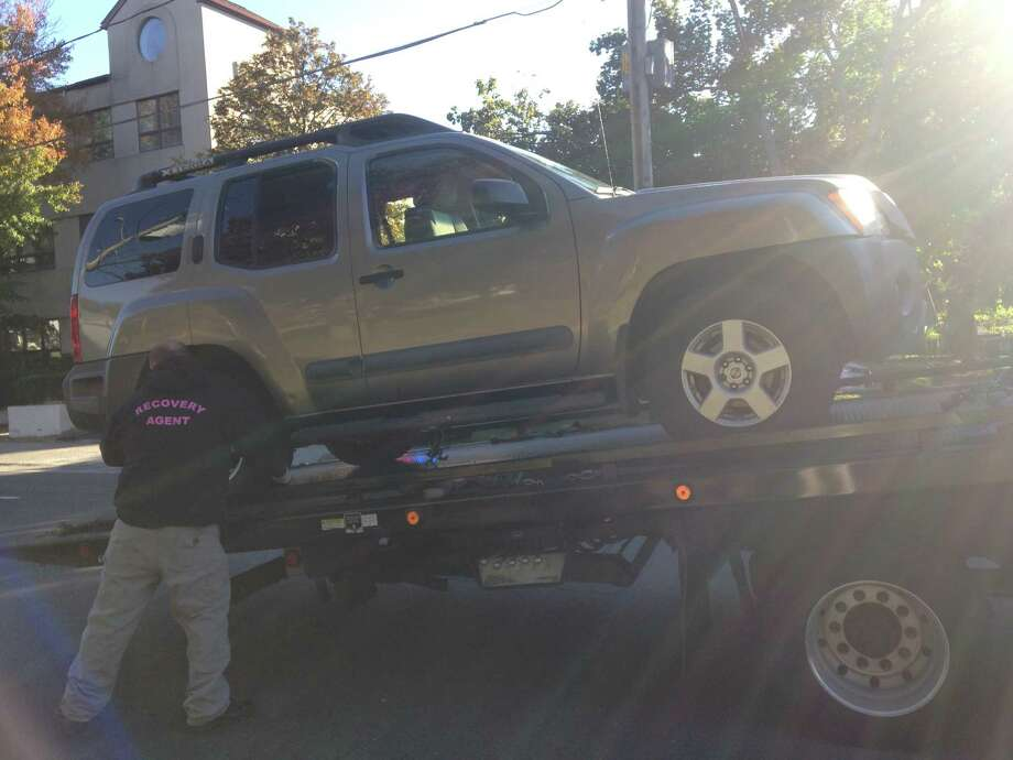 An employee with Federal Towing removes a Nissan Xterra that police say hit a pedestrian at the intersection of North Street and Madison in Danbury Tuesday morning. Photo: /