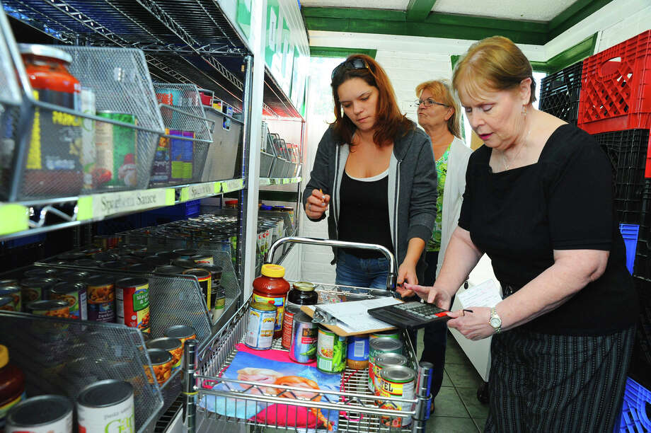 Volunteer Tonee Ruiz , left, and Pat Whitfield, right, help Sherry Lopez with her food shoping at Cypress Assistance Ministries. Photo: Tony Gaines, Photo