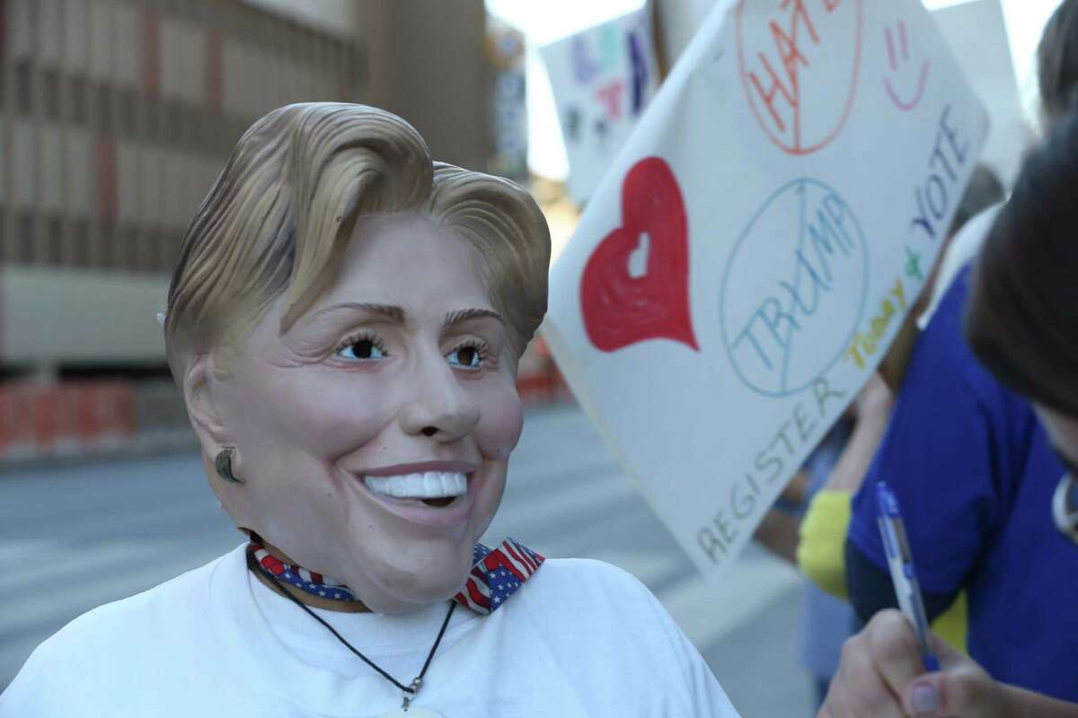 Elena Gonzales and others protesters gather outside the Grand Hyatt Regency where Republican presidential nominee Donald Trump attends a fundraiser in San Antonio, Tuesday, Oct. 11, 2016.