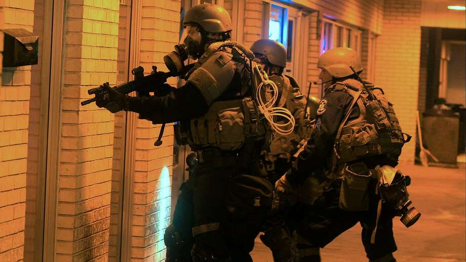 """Police prepare to raid a Ferguson, Mo., storefront in """"Do Not Resist,"""" a grab bag of a documentary about the militarization of police. Photo: Vanish Films"""