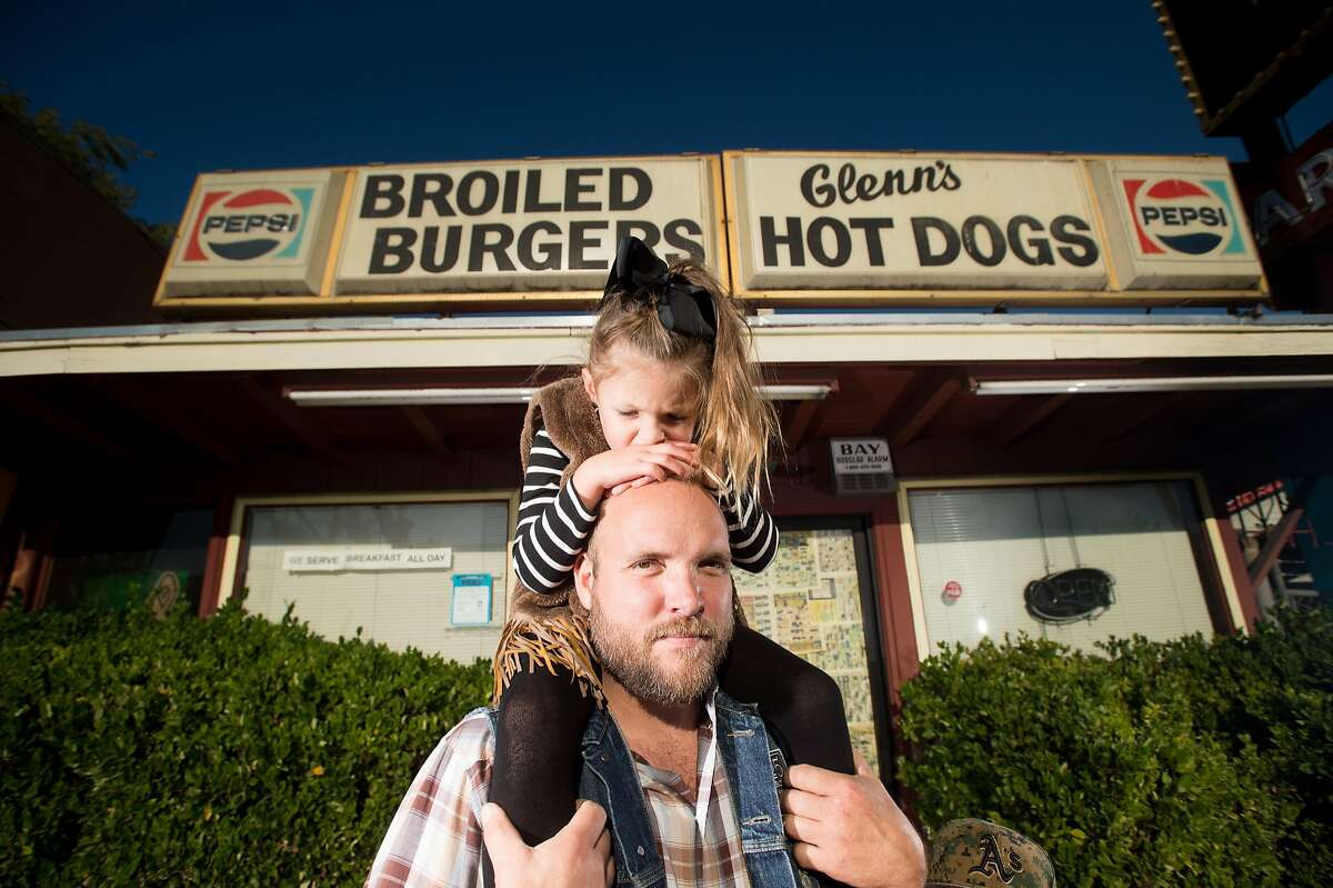 Ryan Farr, founder of 4505 Meats, stands with his daughter Scarlett Farr, 4, outside the future home of 4505 Burgers & BBQ in Oakland, Calif., on Monday, Oct. 10, 2016.