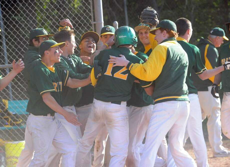 Trinity Catholic's Pat Murphy, 12, celebrates with the team after scoring the winning run in the bottom of seventh as Trinity Catholic hosts Stamford High School in a boys baseball game Monday afternoon, May 10, 2010.  Trinity won 5-4. Photo: Keelin Daly / Stamford Advocate
