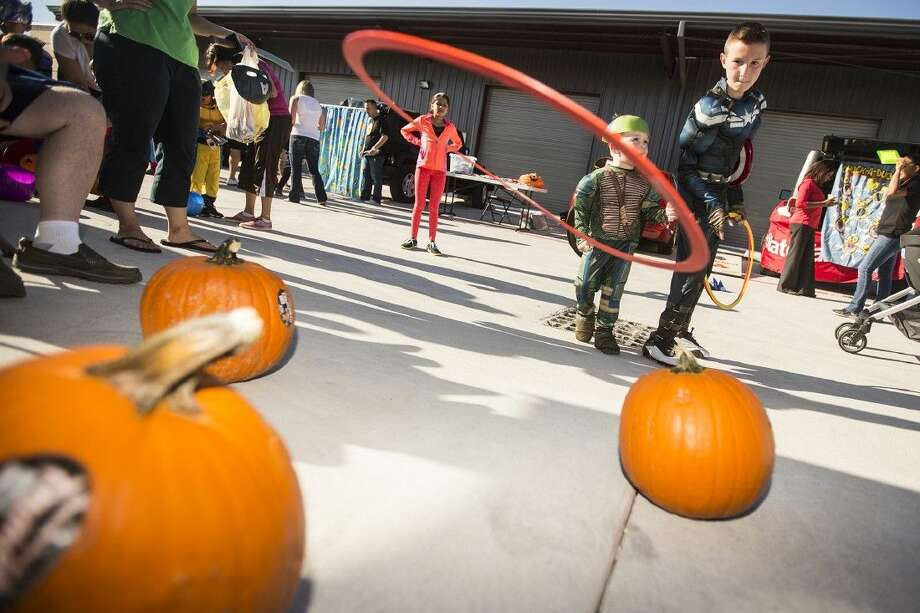 "Travis Lipp attempts to throw rings over pumpkins during Trunk or Treat on Oct. 25, 2014, at JC Sports in Atascocita. The business is the winner of ""The Pitch,"" a contest launched by BBVA Compass and the Houston Dynamo. Photo: ANDREW BUCKLEY"