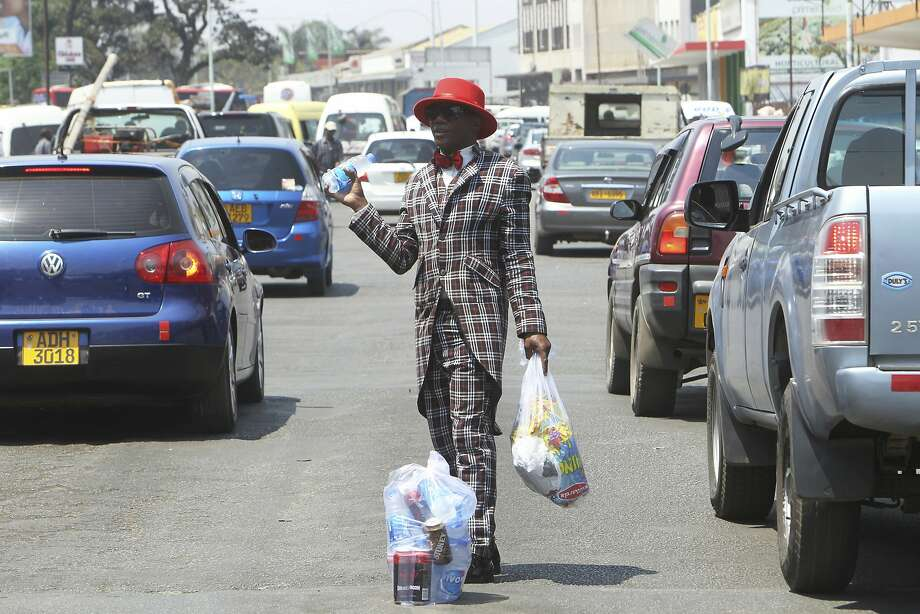 Street vendor Farai Mushayademo dons a three-piece suit to sell water and potato chips to motorists in Harare, Zimbabwe. Photo: Tsvangirayi Mukwazhi, Associated Press