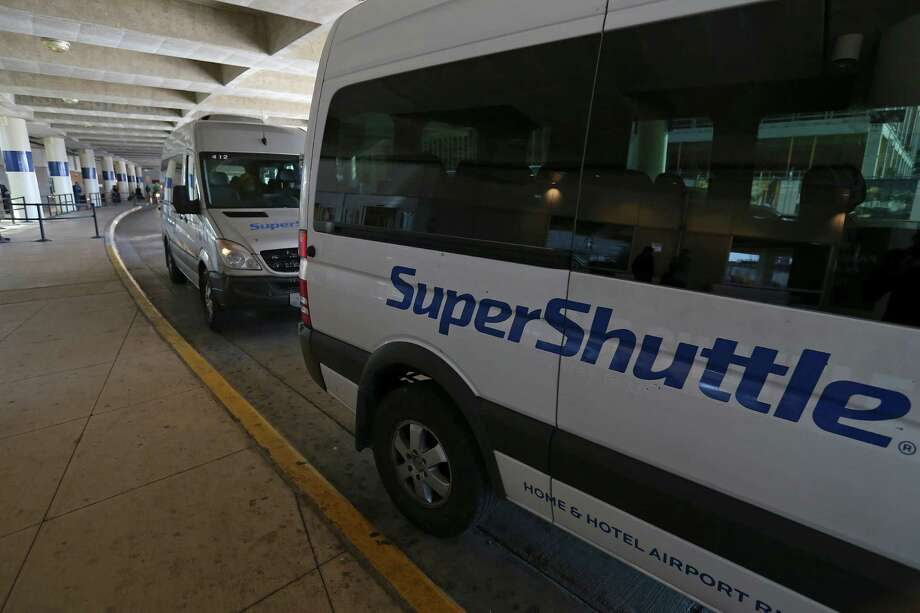 Super Shuttle vans wait for passengers at the San Antonio International Airport on Monday. The shared-ride service will continue to operate at the airport at least for the next couple of months under a resolution reached with the city prior to a bankruptcy court hearing Tuesday. Photo: Edward A. Ornelas /San Antonio Express-News / © 2016 San Antonio Express-News