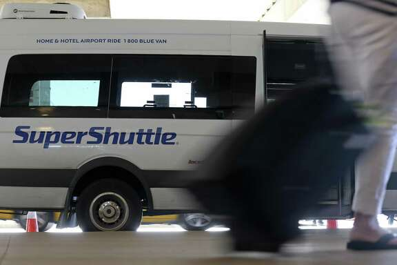 A SuperShuttle waits for passengers at the San Antonio International Airport in October. SuperShuttle is discontinuing its downtown hotel shuttle service at the end of the month at the airport.