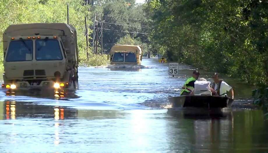 Members of South Carolina National Guard drive through deep water, as well as local rescue personnel in boats carrying dozens of evacuees from the flooded town of Nichols. Photo: MASTER SGT. CARL CLEGG, AFP/Getty Images