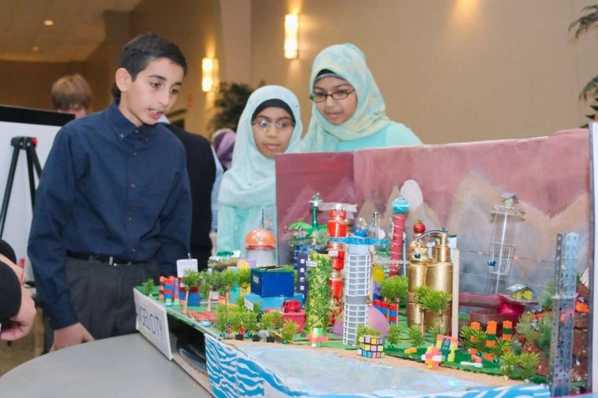 Al-Hadi School students Kazim Mirza, Hiba Hassan and Samana Fatima present their project to judges during the Future City Competition, Tomorrow's Transit: Design A Way To Move People In And Around Your City?