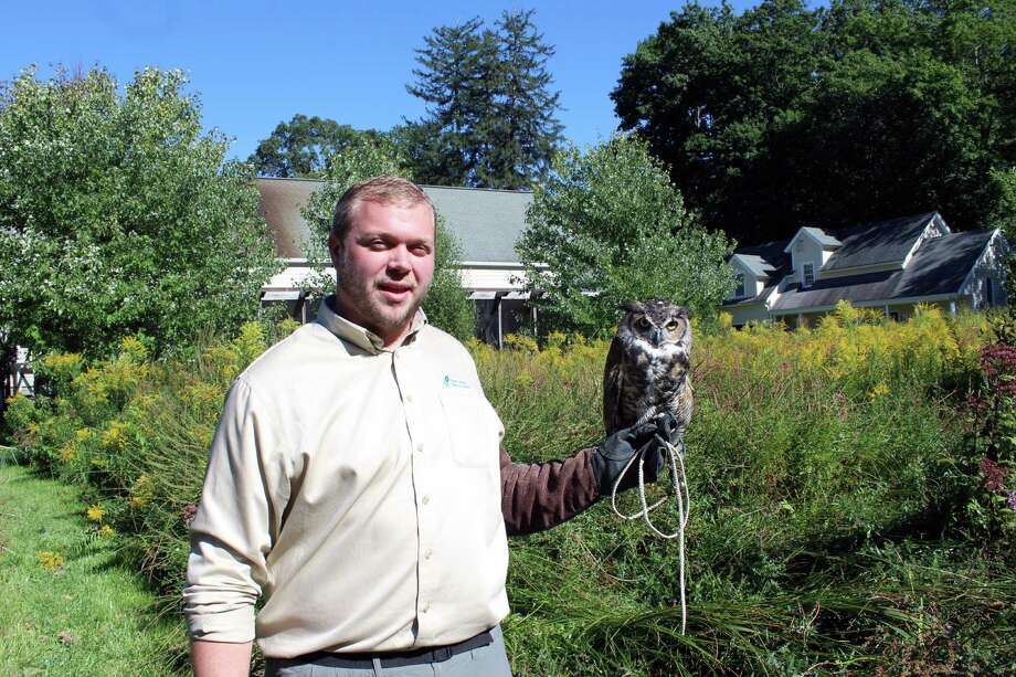 Bill Flynn, of the New Canaan Nature Center, with Socrates, the Great horned owl, on Monday. Photo: Justin Papp / Hearst Connecticut Media / New Canaan News