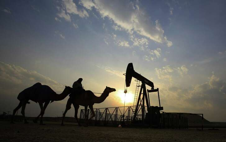 A man rides a camel through the desert oil field and winter camping area of Sakhir, Bahrain in 2015. OPEC nations agreed to reduce their production to help boost global oil prices. The cartel might renew that soon.