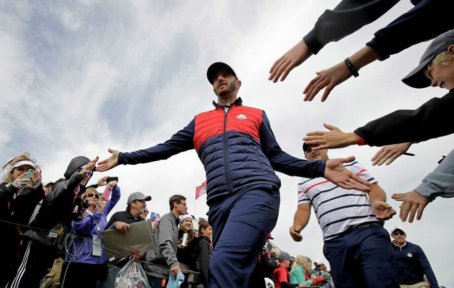 FILe - In this Sept. 27, 2016, file photo, United States' Dustin Johnson is greeted by fans as he walks to the eighth hole during a practice round for the Ryder Cup golf tournament, at Hazeltine National Golf Club in Chaska, Minn. Johnson made it a clean sweep of the tour's biggest honors that are named after its most prominent players. He won the Jack Nicklaus Award as player of the year, the Arnold Palmer Award for leading the money list and the Byron Nelson Award for having the lowest adjusted scoring average. (AP Photo/Charlie Riedel, File) Photo: Charlie Riedel, STF / Copyright 2016 The Associated Press. All rights reserved.