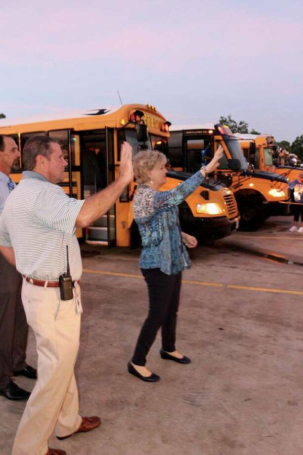 Friendswood ISD Superintendent Trish Hanks, Deputy Superintendent Thad Roher and Director of Transportation Dean Lewis wave to each bus as it rolls out of the bus barn to pick up students on the first day of the Fall, 2016 school semester Monday (Aug. 22). Photo: D OWEN