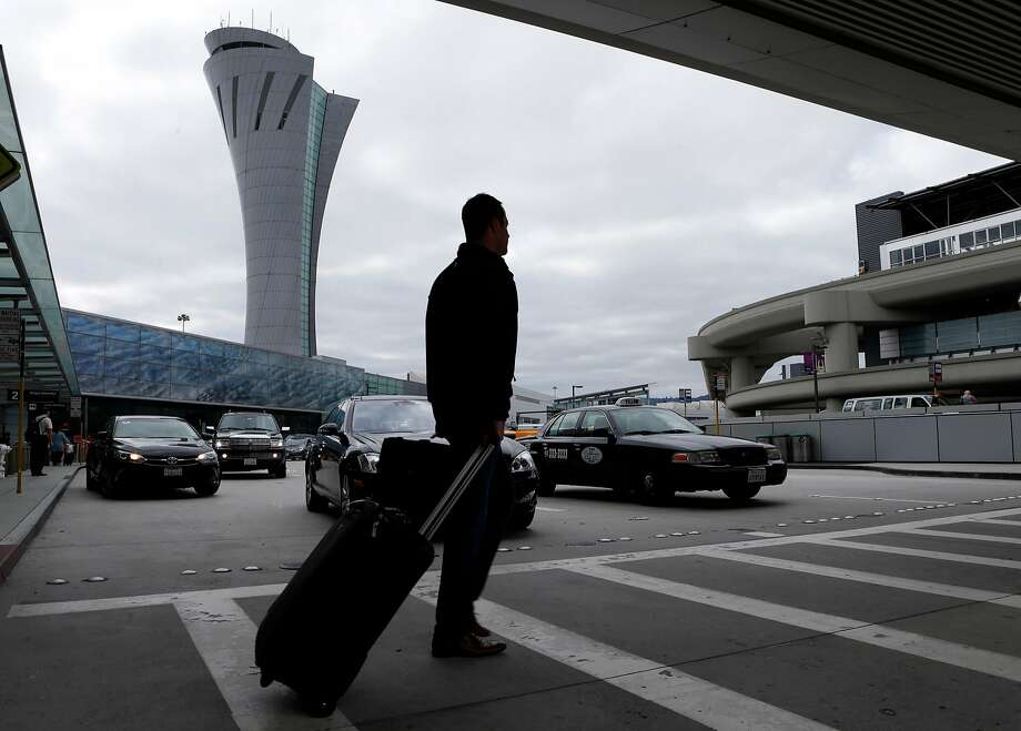 An arriving passenger walks past the new SFO air traffic control tower between terminals one and two in San Francisco, Calif. on Tuesday, Oct. 11, 2016. The iconic 221-foot tall FAA tower becomes fully operational Saturday. Photo: Paul Chinn, The Chronicle
