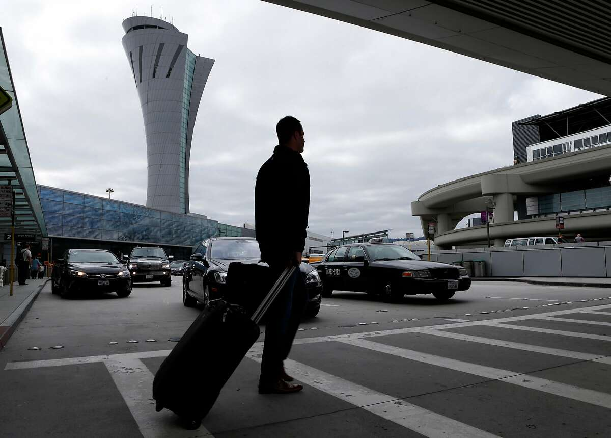 An arriving passenger walks past the new SFO air traffic control tower between terminals one and two in San Francisco, Calif. on Tuesday, Oct. 11, 2016. The iconic 221-foot tall FAA tower becomes fully operational Saturday.