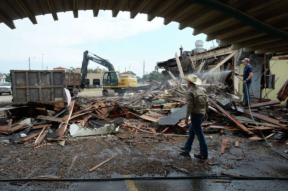 Matthew Behnken waters down dust while Richard Behnken orchestrates the demolition of the Pig Stand in Beaumont on Tuesday.  Photo taken Tuesday, October 11, 2016 Guiseppe Barranco/The Enterprise Photo: Guiseppe Barranco, Photo Editor
