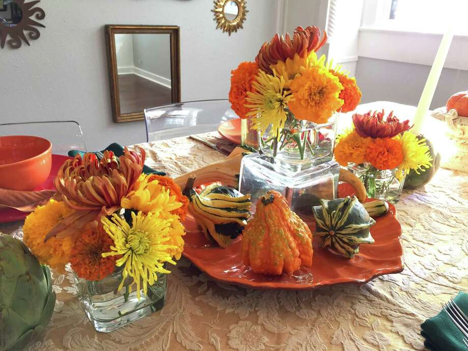 Classic fall tablescape: I found the dishware and glasses at the Dollar Tree store, so a placesetting for four cost $16 for a plate, bowl, goblet and glass. These may not be the heirlooms I bequeath in my will, but for a fun party, paying $1 per piece of colorful dish or glassware seems worth it. Grocery and big-box stores almost all have bags of these mini-pumpkins, and they're classic for good reason: They last at least a month and they're easy to move around your home for a pop of fall anywhere. Photo: Emily Spicer / San Antonio Express-News