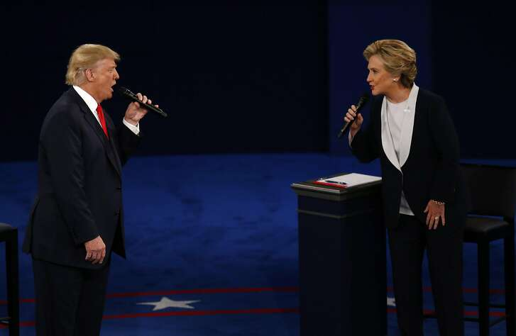 Donald Trump, 2016 Republican presidential nominee, and Hillary Clinton, 2016 Democratic presidential nominee, speak during the second U.S. presidential debate at Washington University in St. Louis, Missouri, U.S., on Sunday, Oct. 9, 2016. As has become tradition, the second debate will resemble a town hall meeting, with the candidates free to sit or roam the stage instead of standing behind podiums, while members of the audience -- uncommitted voters, screened by the Gallup Organization -- will ask half the questions. Photographer: Andrew Harrer/Bloomberg