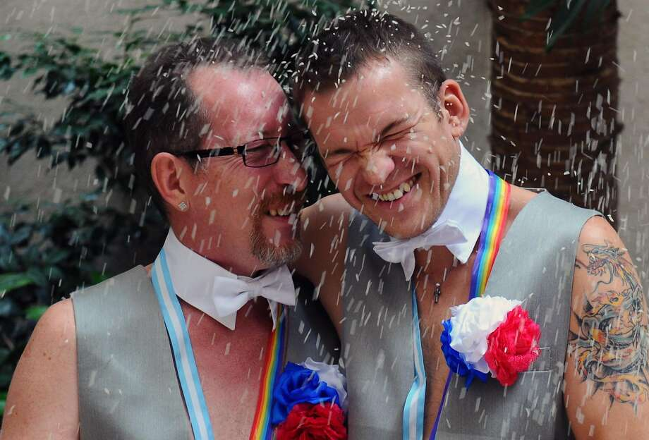 Russian Alexander Emereev (L) and Dmitry Zaytsev smile after getting married in Buenos Aires in 2014. Photo: DANIEL GARCIA�/ AFP, AFP/Getty Images