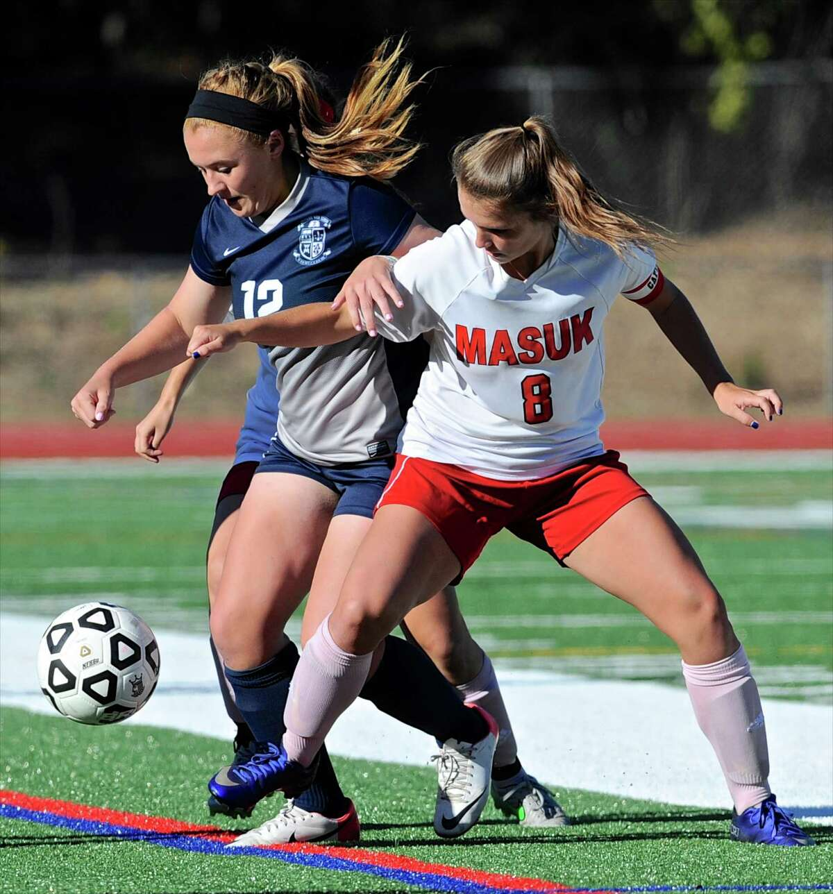 Immaculate's Kayla Lanza (12) and Masuk's Nikki Bisesi (8) battle over the ball in the SWC girls soccer game between Immaculate and Masuk high schools, on Tuesday afternoon, October 11, 2016, at Masuk High School, in Monroe, Conn.
