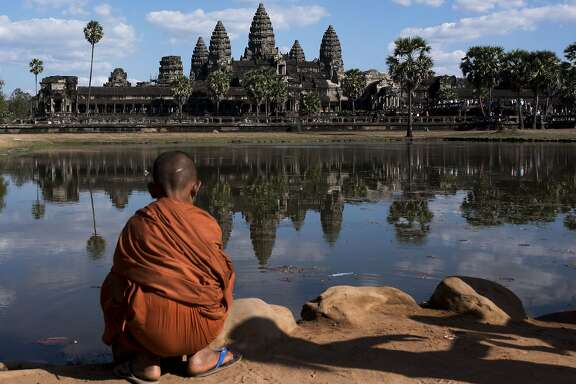 SIEM REAP, CAMBODIA - JANUARY 13: A young monk sits in front of the Angkor Wat temple reflected on a lake on January 1, 2016 in Siem Riep, Cambodia. Angkor was the capital city of Khmer Empire, which flourished from approximately the 9th to 15th centuries. Angkor was a megacity supporting at least 0.1% of the global population during 1010-1220. The city houses the magnificent Angkor Wat, one of Cambodia's popular tourist attractions. (Photo by Xaume Olleros/Getty Images)