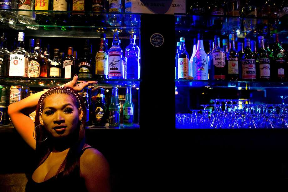 A Cambodian transexual bar girl hangs out inside a bar waiting for customers in Phnom Penh. Photo: Paula Bronstein, Getty Images