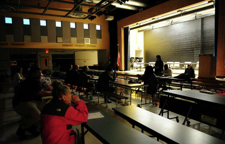 Several members of the Bridgeport Board of Education hold a meeting even after the cafeteria lights were turned out on them at Geraldine Johnson School in Bridgeport, Conn., on Tuesday Oct. 11, 2016. The BOE meeting scheduled for tonight was canceled last week by Dennis Bradley, the board chairman. Bradley is one of several members boycotting regularly scheduled meetings until fellow board member Maria Pereira resigns. Photo: Christian Abraham / Hearst Connecticut Media / Connecticut Post
