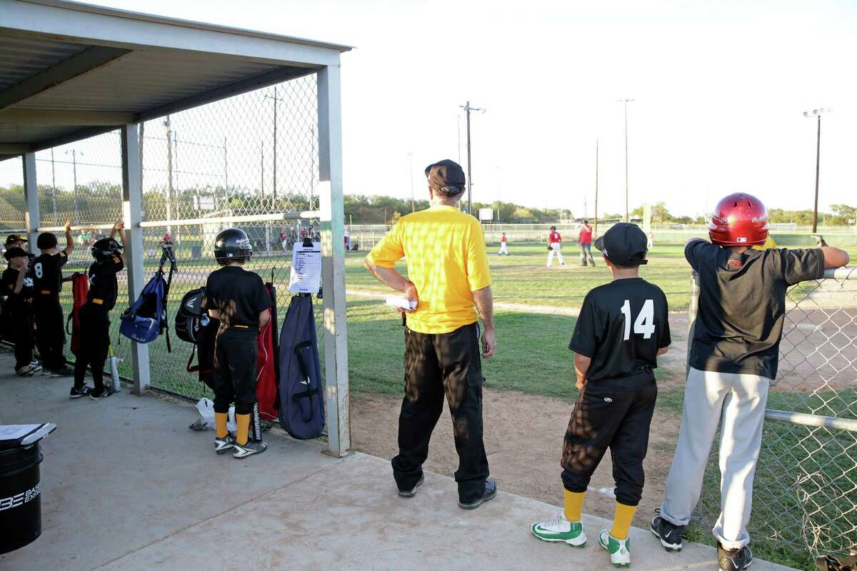 Little Leaguers watch their team from the dugout as fans of the Capitol Park Little League gather at a rally to support efforts to find a new location on Oct. 11, 2016. The fields are now off of Bulverde Road.