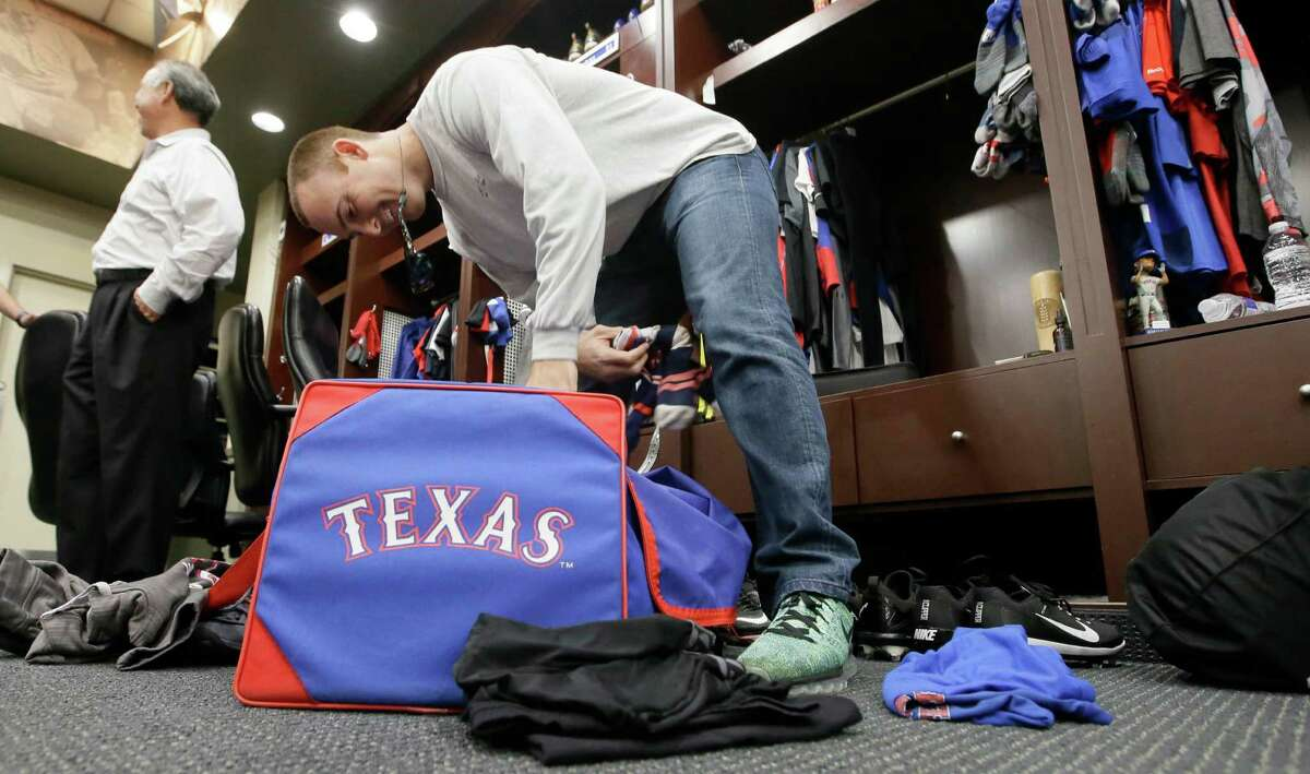 Texas Rangers pitcher Sam Dyson packs a bag in the locker room at the baseball park in Arlington, Texas, Tuesday, Oct. 11, 2016. Texas was swept out of the ALDS by the Toronto Blue Jays. (AP Photo/LM Otero)