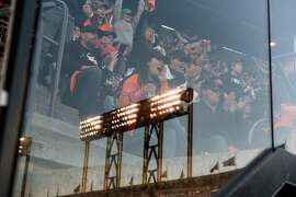 A stadium light is reflected in a glass panel as fans cheer during game 4 of the National League Division Series between the Chicago Cubs and the San Francisco Giants at AT&T Park in San Francisco, CA Tuesday, October 11, 2016.