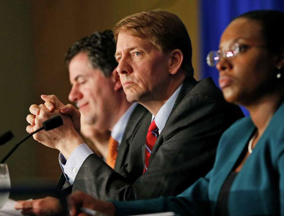 Consumer Financial Protection Bureau Director Richard Cordray, center, listens during a panel discussion in 2015. Some Republican lawmakers want him fired.  Photo: Steve Helber, STF / Copyright 2016 The Associated Press. All rights reserved. This material may not be published, broadcast, rewritten or redistribu