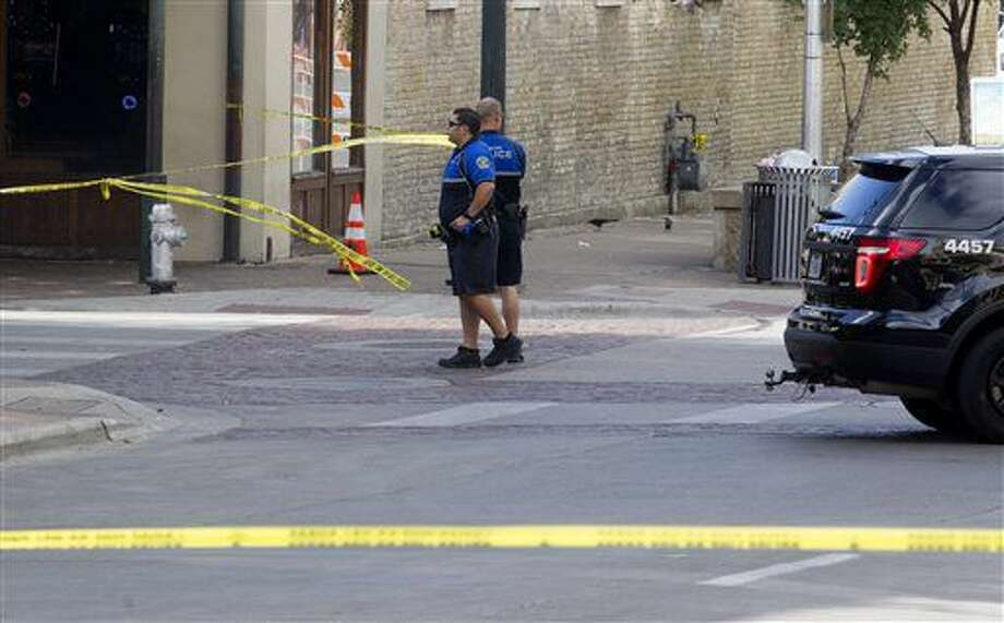 Police tape off areas on East 6th street in Austin, Texas, where a woman was fatally shot and several others wounded early Sunday, July 31, 2016. Police are still searching for the shooter, who opened fire in a crowded entertainment district in downtown Austin. (Jessalyn Tamez/Austin American-Statesman via AP) Photo: Jessalyn Tamez