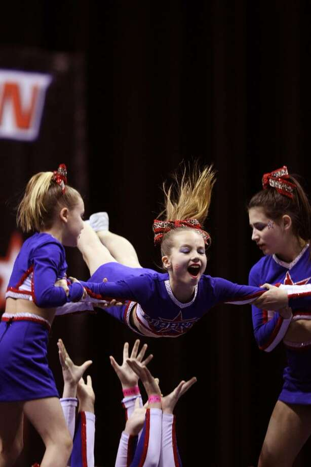 Liberty Senior Stars cheerleaders Erika Bloes, left, of Riverside, Shelby Hopper, center, of Riverside, and Amanda Friedlander, right, of Cos Cob, are captured in action in the center of the pyramid. Photo: Contributed Photo / Greenwich Citizen
