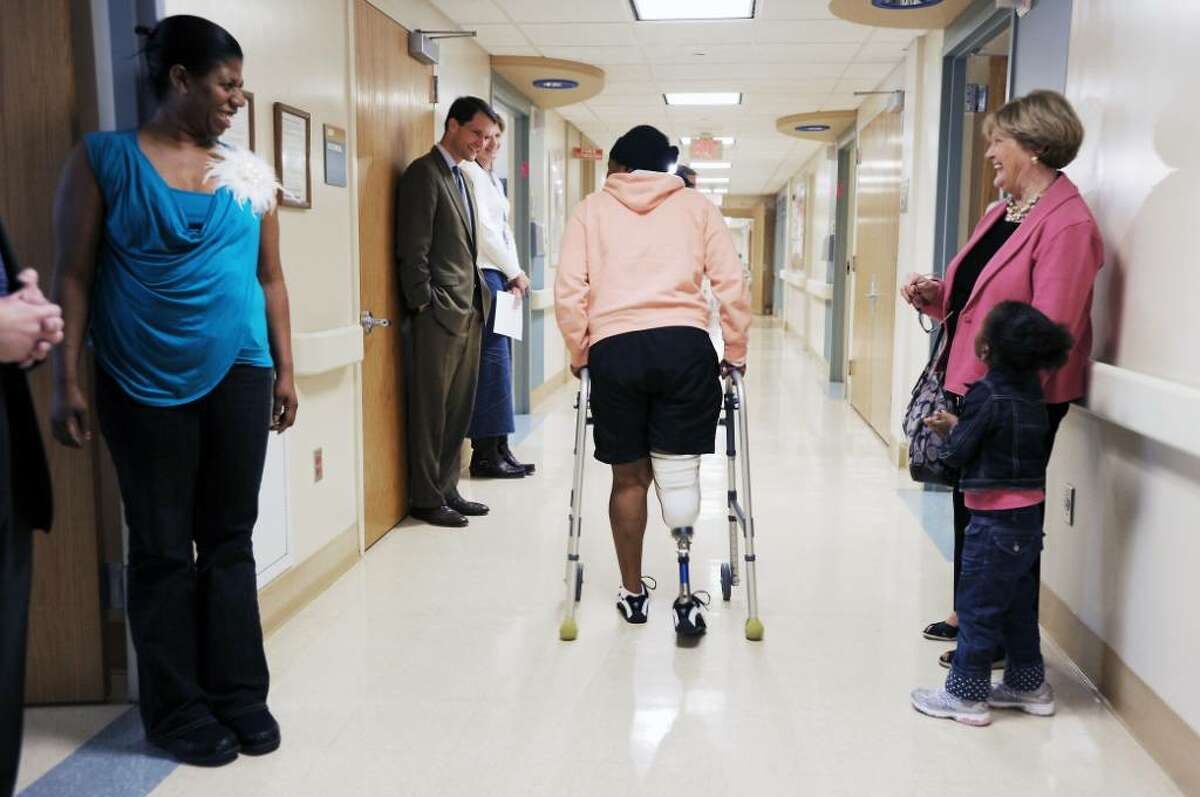 Martine Volcimus walks the halls at Stamford Hospital testing out her new prosthetic leg as her sister Minouche Gilles and Congressman Jim Himes look on in Stamford, Conn. on Tuesday May 11, 2010. Volcimus, from Haiti, lost her leg in the Haitian earthquake in January. Gilles adopted a three-year-old girl, Angela, from Haiti after the earthquake.