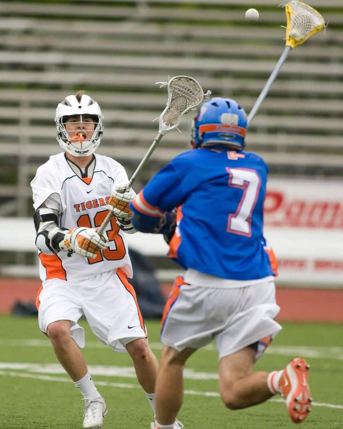 Ridgefield's Aidan Scott (13) sets up a Tiger goal by flicking a pass over the head of Danbury's Austin Lee to teammate Mike Galione, who scored on the play Tuesday at Ridgefield High.