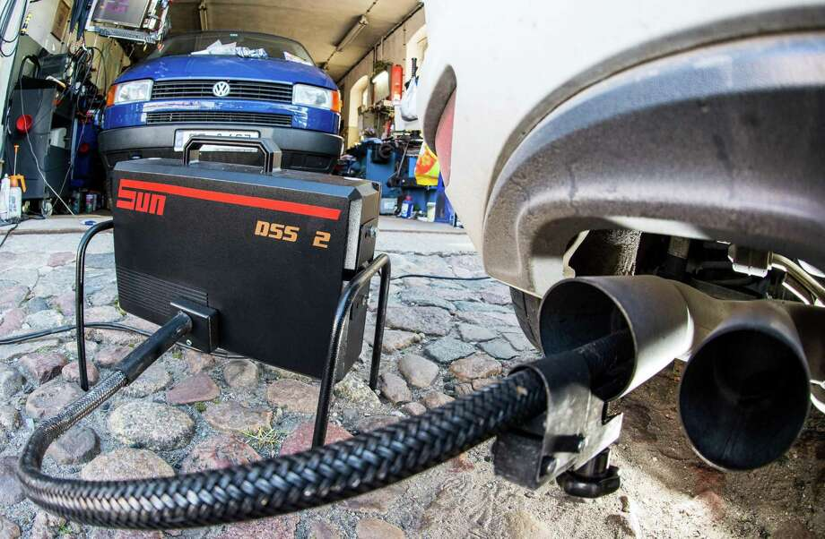 Picture taken on October 1, 2010 in a car workshop in Frankfurt an der Oder, eastern Germany, shows a measuring tube sticking in the exhaust pipe of a Volkswagen Golf 2,0 TDI car during an emissions test. Public debate is raging in Germany over whether top executives at Volkswagen should be paid generous bonuses as the carmaker struggles to stem further fallout from its massive engine-rigging scandal. / AFP PHOTO / dpa / Patrick Pleul / Germany OUTPATRICK PLEUL/AFP/Getty Images Photo: PATRICK PLEUL / AFP/Getty Images / DPA