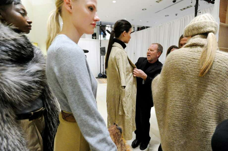 World-renowned designer Michael Kors looks the models over before the show as he recreates his Bryant Park Fashion Week 2010 show presenting his fall collection at Richards of Greenwich Tuesday, May 11, 2010. After the show Kors held a trunk show greeting flocks of shoppers. The trunk show will be hosted by Kors' associates at Richards running through Thursday and then move to Mitchells in Westport for Friday and Saturday. Photo: Keelin Daly / Stamford Advocate