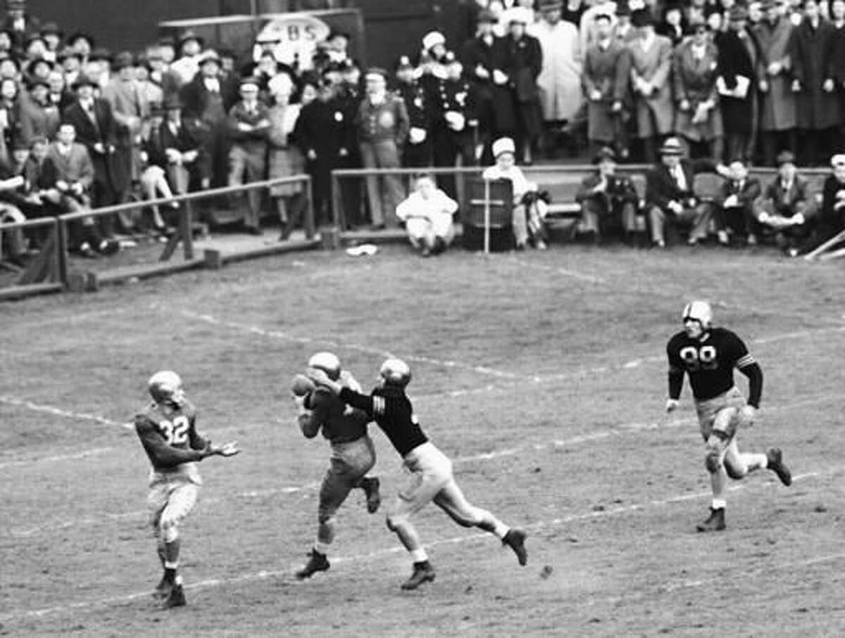 FILE - In this Nov. 9, 1946, file photo, Notre Dame's Emil Sitko (14) grabs a pass intended for Army's Bill West, center right, during the fourth quarter of a college football game at Yankee Stadium in New York. Notre Dame quarterback John Lujack (32) holds out his hands for a possible lateral. The game ended in a scoreless tie. (AP Photo/Harry Harris, File)