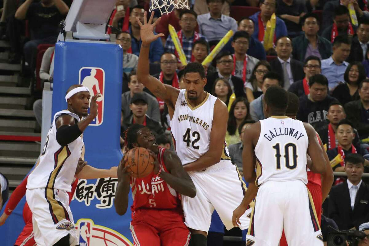 Alexis Ajinca of the New Orleans Pelicans, center in white tries to block Montrezl Harrell of the Houston Rockets during a preseasons match in Beijing, China, Wednesday, Oct. 12, 2016. (AP Photo/Ng Han Guan)