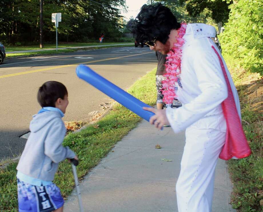 Kindergartner Devon Havens laughs at physical education teacher Josh MacDonald  dressed as Elvis to promote school spirit on Walk to School Day for South School in New Canaan, CT on Oct. 7, 2016. Photo: Erin Kayata / Hearst Connecticut Media / New Canaan News